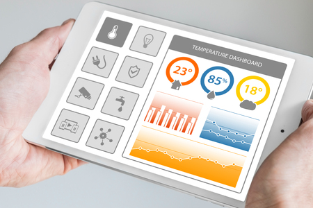 Smart Home Automation Control Dashboard to smart devices and sensors in the house or apartment. Hand holding modern tablet.