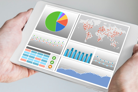 dash: Business man holding tablet with dashboard in his hand. Dashboard displays business KPIs and charts in order to monitor and control the business