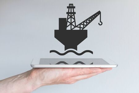 triplet: Concept of digital and mobile oil and gas business. Hand holding modern smart phone or tablet.