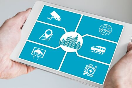 holding smart phone: Smart City concept. Hand holding tablet or smart phone with icons of connected devices.