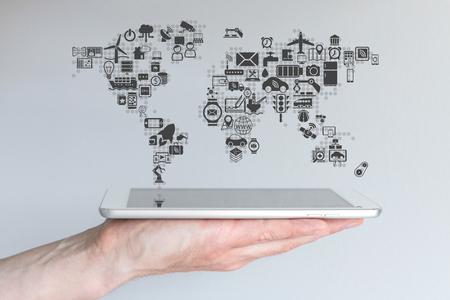 グローバル モバイル デバイス、物事のインターネットの概念。現代のスマート フォンやタブレットで中立的な背景を持っている手。 写真素材