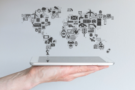 Global mobile devices and the Internet of Things concept. Hand holding modern smart phone or tablet with a neutral background.