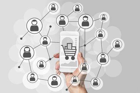 friend chart: Digital marketing and mobile sales concept with hand holding modern smart phone and social network of consumers