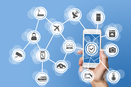 Internet of things security concept illustrated by hand holding modern smart phone with connected sensors in objects. Stock Photo
