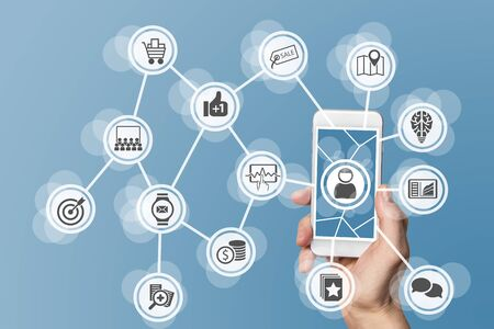 mobile marketing: Online mobile marketing by leveraging big data, analytics and social media. Concept with hand holding modern smart phone Stock Photo