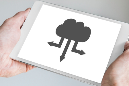digitization: Cloud computing symbol for upload and download Displayed on touch screen of a modern tablet.