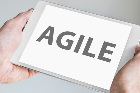 agile: Agile text Displayed on touchscreen of modern tablet or smart device. Concept of modern software development methodology for smartphones. Stock Photo