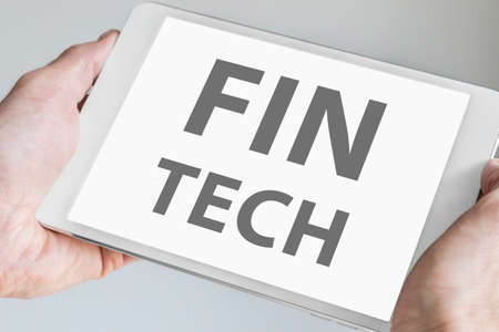 disruption: Fin tech text Displayed on touchscreen of modern tablet or smart device. Concept of financial technology startup company. Stock Photo