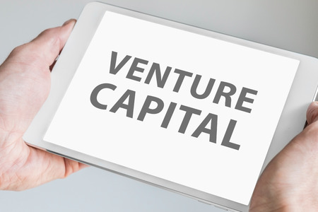capitalist: Venture capitalist text Displayed on touchscreen of modern tablet or smart device. Stock Photo