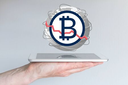 Decline of global bitcoin currency exchange rate concept with hand holding tablet Stock Photo
