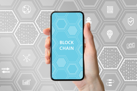 Blockchain and cryptocurrency concept. Hand holding modern bezel-free smartphone in front of neutral background.