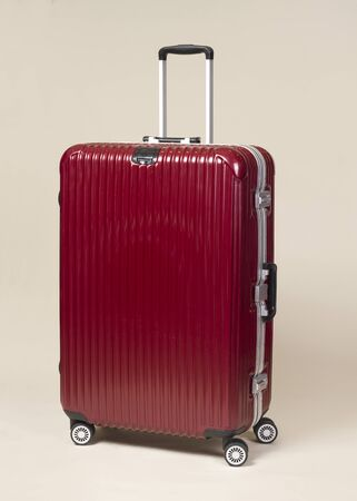 hard stuff: Red large trolley suitcase with silver handle on beige background Stock Photo
