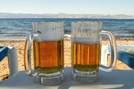 drafts: Two Beer drafts at the beach with sea and sand view