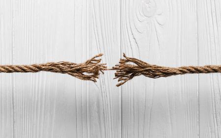Cuerda deshilachada a punto de romperse sobre fondo blanco de madera Foto de archivo