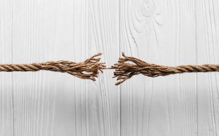 Rope frayed about to break on Wooden white background Banco de Imagens - 97939878