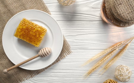 Honey comb on white plate and glass jar on wooden table