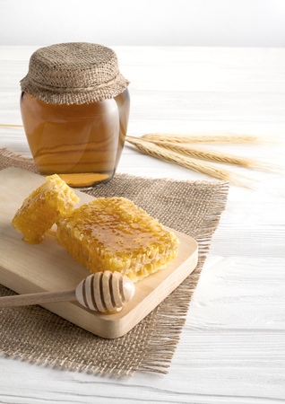 Honeycomb and glass jar on white wooden table - vertical photo Stock Photo