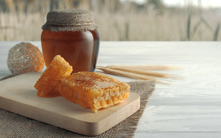 Honey comb and honey jar on wooden table and wheat field in the background