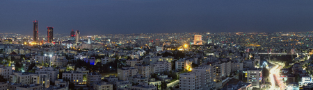Panoramic view of Amman city skyline from Abdali area to through Amman mountain to Abdoun bridge at night