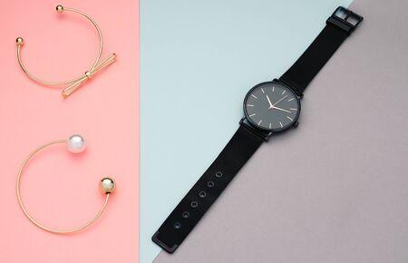 Black modern wrist watch with two golden bracelets on pastel color background Banque d'images