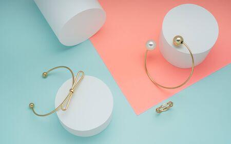 Pulseras de oro y anillo de oro sobre fondo de colores pastel - Diseño de lazo y pulseras de perlas doradas sobre fondo rosa y verde