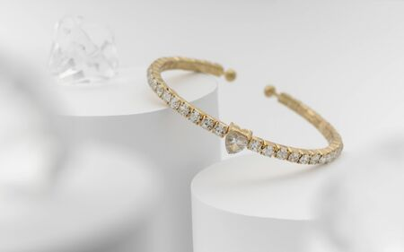 Pulsera de oro y diamantes en forma de corazón sobre fondo blanco.