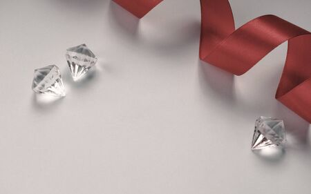 Top view of diamonds and red ribbon on white background 写真素材