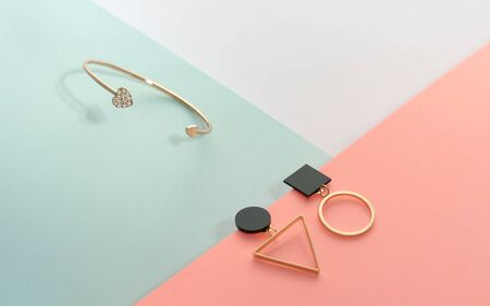 Heart shape golden bracelet and geometric modern Earrings pair on blue and pink background