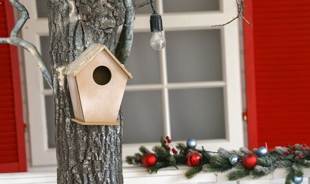 hanged Wooden bird house on tree in decorated house garden
