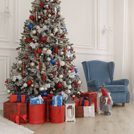 Red gift boxes under Christmas tree and blue armchair behind.