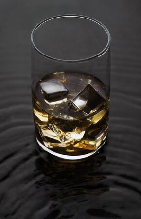 Whiskey Glass with ice on wavy liquid surface.Alcoholic drink with ice cubes on wet surface. Reklamní fotografie