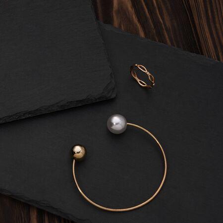 Golden pearl bracelet and golden ring on black stone plate Reklamní fotografie
