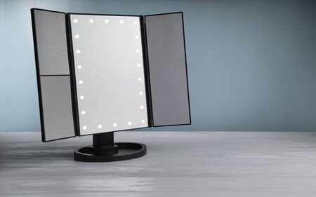 LED vanity Make up mirror on white table with blue background. Magnifying LED multiple mirrors