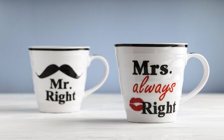 Two mugs with printed text Mr. right and Mrs. always right. Funny phrase about couples life printed on mug