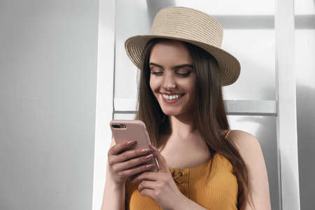Portrait of attractive girl wearing straw hat and using smartphone with copy space