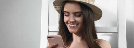 Panoramic close up of a brunette girl wearing straw hat and using smartphone with copy space
