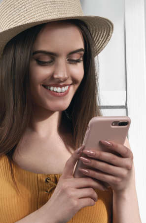 Vertical portrait of a cheerful girl using a smartphone