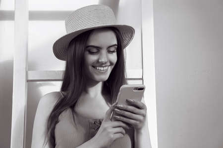 Black and white portrait of young Girl using smartphone and smiling with copy space Stock fotó