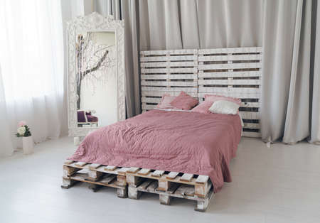 Queen size bed made of wooden pallets and large wooden mirror in bright bedroom