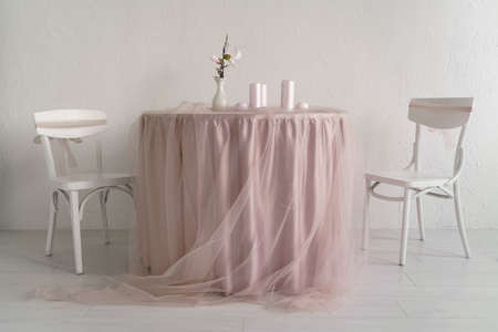 Two white chairs and covered table with pink table clothes