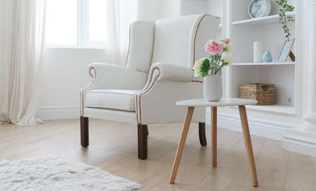 Leather white armchair and modern wooden table with flowers vase in bright room Foto de archivo