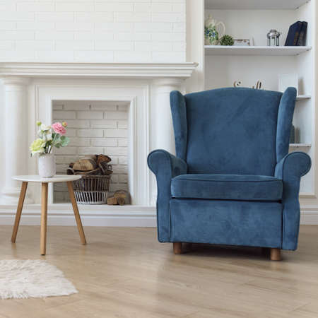 Navy blue classic armchair and flower vase on modern white wooden table in front of fireplace