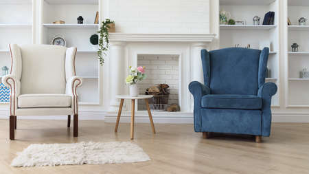 White and blue armchair with white modern table in front of fireplace in living room