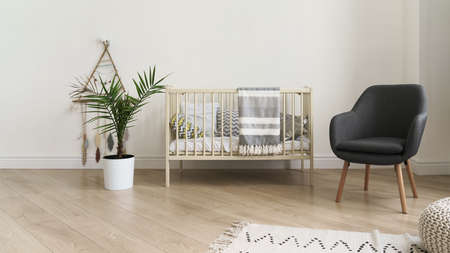 Cot bed and modern gray chair and indoor plant in baby bedroom