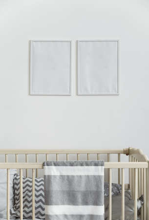 Two white empty wall frames above infant baby cot bed