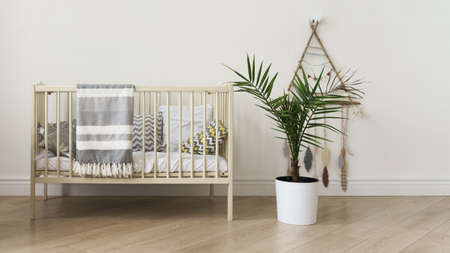 New born baby cot bed and indoor palm in a pot Foto de archivo