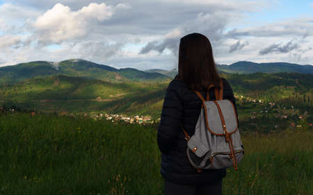 Woman with backpack looking at view of mountains