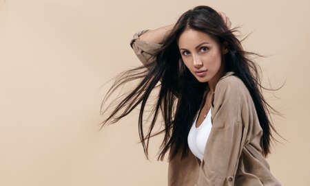 Portrait of brunette girl with healthy long hair on beige background with copy space