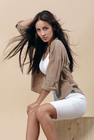 Brunette attractive girl wearing casual clothes with flying hair sitting on wooden chair
