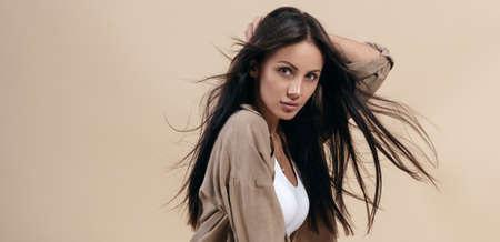 Portrait of pretty brunette girl with healthy long hair on beige background Stock fotó